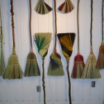 A selection of kitchen broom on the back wall of the Broom Shop